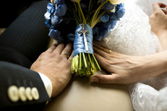 Noivos que guardam as mãos no ramalhete do casamento no carro Fotos de Stock Royalty Free