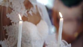 Noivos que guardam velas na igreja na cerimônia filme