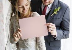 Noivos Showing Blank Paper no dia do casamento fotos de stock