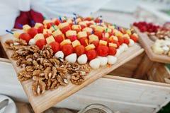 Noix avec la tomate-cerise, le fromage et les oeufs de caille au conseil en bois Images stock