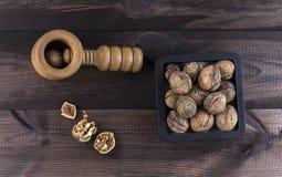 Noix avec le casse-noix sur le fond en bois Photos libres de droits