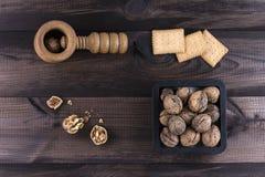 Noix avec le casse-noix sur le fond en bois Image libre de droits