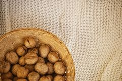 Noix dans le panier avec les feuilles et la tasse sèches de thé sur le fond à carreaux brun Image stock