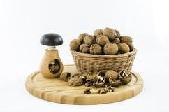 Noix dans le panier en osier sur le conseil en bois Photos stock