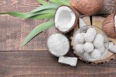 Noix de coco avec des moitiés de noix de coco, de copeaux de noix de coco et de bonbons sur un fond en bois brun image libre de droits