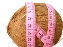 Noix de coco avec le ruban métrique rose au-dessus du fond blanc (concept de photographie stock libre de droits