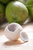 Noix de coco d'épluchage sur le plancher en bois avec le fond vert de noix de coco Images stock