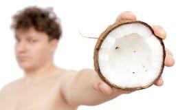 Noix de coco dans une main du ` s d'homme sur un fond blanc Photographie stock libre de droits