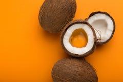 Noix de coco demi avec le jaune d'oeuf à l'intérieur au fond jaune Photo stock
