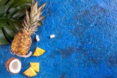 Noix de coco et ananas coupés en tranches dans la maquette bleue de vue supérieure de fond d'été de conception exotique de fruit photographie stock libre de droits