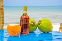 Noix de coco et bouteille de boisson alcoolisée sur la table par la plage Image libre de droits