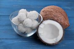 Noix de coco et demi noix de coco avec des sucreries de noix de coco sur un fond bleu Photos libres de droits