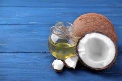Noix de coco et demi noix de coco avec de l'huile de noix de coco sur un fond bleu Photos stock