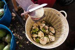 Noix de coco et peau dans le panier, couteau sur la table en bois sur le lieu de travail image libre de droits