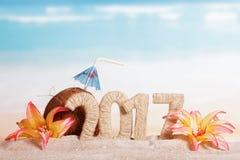 Noix de coco, numéro 2017, et fleurs en sable contre la mer Images libres de droits
