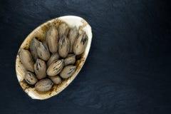 Noix de pécan avec la coquille de noix dans le plat naturel de feuille de banane d'Eco sur la surface en pierre noire de fond ave photographie stock