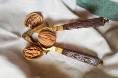 Noix et casse-noix de cru avec la poignée en bois découpée image libre de droits