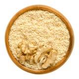 Noix moulues et moitiés de noyau de noix dans la cuvette en bois photographie stock