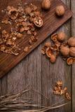 Noix sur le fond rustique de conseil en bois avec l'espace de copie de paille pour le texte Photographie stock libre de droits