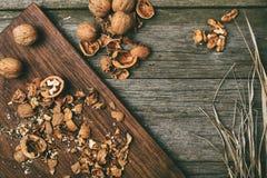 Noix sur le fond rustique de conseil en bois avec l'espace de copie de paille pour le texte Photo stock