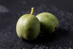 Noix vertes fraîches dans la peau juste de l'arbre Noix sur un fond noir Macro Image libre de droits