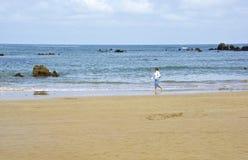 Noja Spanien - April 2nd 2015: Kvinnan promenerar stranden av Noja Royaltyfri Bild