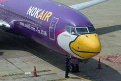 NokAir aircraft Airbus A320. Passengers aircraft Airbus A320 by NokAir at the Don Mueang airport with a man doing plane to fly Stock Photo