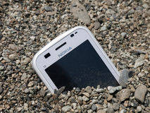 Nokia financial competitive difficulty metaphor. Nokia sinking - bogged down in the sand maybe, following staff layoffs, recent problems with new products and Royalty Free Stock Photo