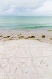 Nolla-och-kors lek på en strand Royaltyfri Bild