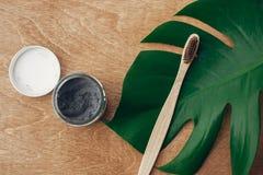 Nollförlorat begrepp Naturlig tandkräm aktiverade kol i exponeringsglaskrus och bambutandborste på träbakgrund med gräsplan arkivfoton