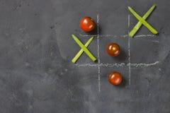 Nollor och korsmatbegrepp med gräsplaner och tomater arkivfoto