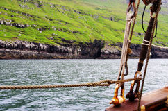Nolsoy - Faroe Islands. View of the cliffs of Nolsoy, one of the Faroe Islands from an old sailing boat stock photography