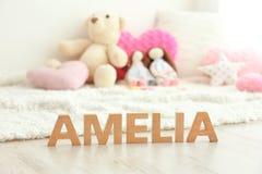 Nom AMELIA de bébé composée de lettres en bois sur le plancher Photographie stock libre de droits