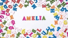 Nom AMELIA de bébé composée de lettres en bois sur le plancher Choix du concept de nom Image libre de droits