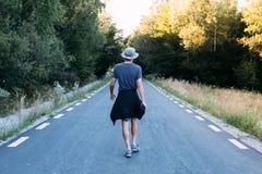 Nomad adventurer in camo hat walks road Stock Photography