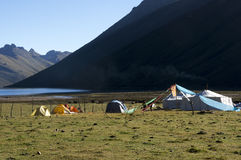 Nomad camp and tourists lakeside. Nomad tents and camp trekkers at a lake in Tibet, Amdo Stock Images