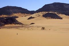 Nomad crossing a vast desert landscape. A single nomad crossing a vast desert landscape in the Acacus Mountains, Sahara desert, Libya stock photos