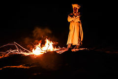 Nomad in the desert. Nomad standing by the fire at night in the sahara desert, Morocco Stock Photos