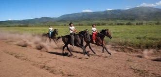 Nomad horse riding competition. LEPSINSK, ALMATY REGION, KAZAKHSTAN - JUL 14, 2008: Boys in traditional national nomad long-distance horse riding competition Royalty Free Stock Photo