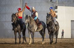 Nomad men after wrestling on horseback, winner is being announced Royalty Free Stock Images