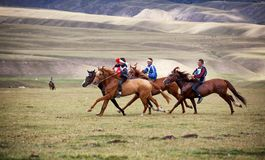 Nomad national horse riding competition. ALMATY REGION, KAZAKHSTAN - AUGUST 12, 2009: Unidentified competitors in action at A traditional national nomad long Stock Images