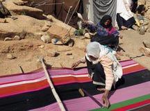 Nomadberberkvinnor som framme väver mattor av deras tält i bergen royaltyfria bilder