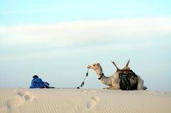 Nomade und Kamel auf einer Sanddüne Lizenzfreies Stockfoto