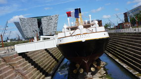 Nomadic & Titanic Belfast. The Nomadic in her dry dock in Belfast with a view of the Titanic Belfast visitor's attraction in the background Royalty Free Stock Image