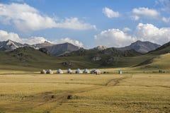 Nomadic yurt camp in Asia. Nomadic yurts camp with mountain range and grassland in Kyrgyzstan stock photo