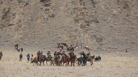 Nomads with eagles riding on horses stock video