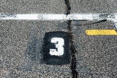 Nombre à trois positions sur le speed-way commençant la voie photographie stock libre de droits