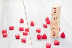 Nombre de la nouvelle année 2018 sur le cube en bois en pile avec le groupe de mini rouge h Photos libres de droits