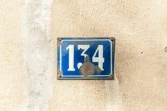Nombre de plaque métallique de vieille de vintage adresse de maison 134 cent trente-quatre sur la façade de plâtre du mur extérie photos stock