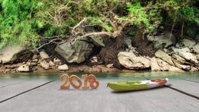 Nombre en bois 2018 et bateau de kayak sur le fond de planche et de forêt humide Photographie stock libre de droits